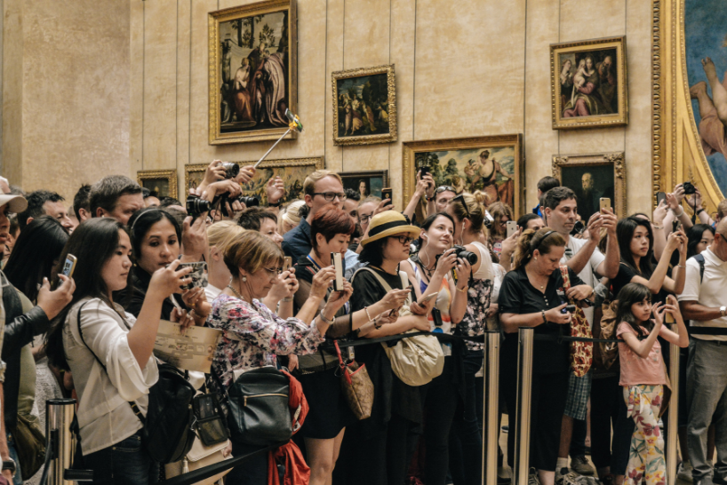 A crowd of people taking photos of an exhibition